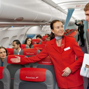 1200px-Austrian_Airlines_flight_attendant_and_passenger-1080x675